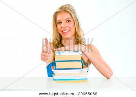 Smiling teengirl sitting at table with books and showing thumbs up gesture