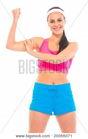 Cheerful fitness young girl in sportswear showing her muscles isolated on white