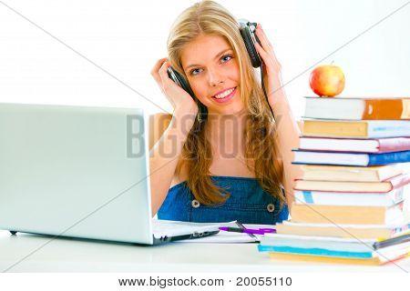 Sentado en la mesa sonriendo teengirl con auriculares escuchando audio lecciones