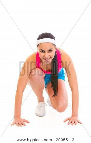 Smiling fitness young girl in start position ready for race isolated on white