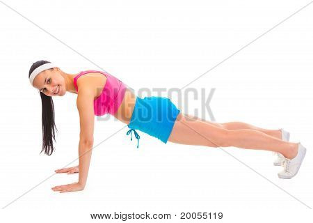 Smiling young sportsgirl doing push-up isolated on white