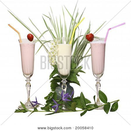 Glass glasses with a dairy cocktail and tubules on a white background with green leaves and a grass