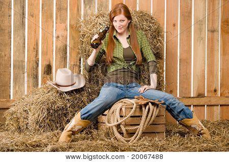 Provokativ junge Cowgirl Bier trinken In Scheune