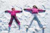 High angle view of cute daughter and mother playing and lying in the snow. Happy woman and smiling l poster