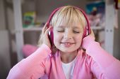 Close-up of cute girl listening to pink headphones poster