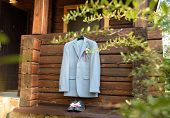 Stylish Elegant Wedding Groom Suit With Boutonniere Hanging On Wooden House Outdoors In Sunny Day. G poster