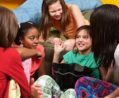 stock photo of  preteen girls  - Little girl sharing a joke with her friends - JPG