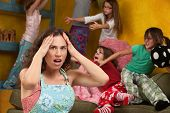 stock photo of pillow-fight  - Upset mother with hands on head among mischievous little girls - JPG