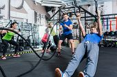 Men and women at functional fitness training in gym doing sport on rings and rope poster