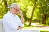old age, retirement and people concept - thoughtful senior man in glasses sitting on bench at summer poster
