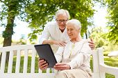 old age, technology and people concept - happy senior couple with tablet pc computer in city park poster