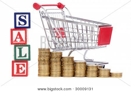 Coins in the form of the diagramme, shopping cart and word SALE