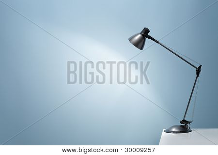An office desk lamp illuminating the background. Lots of copy space.