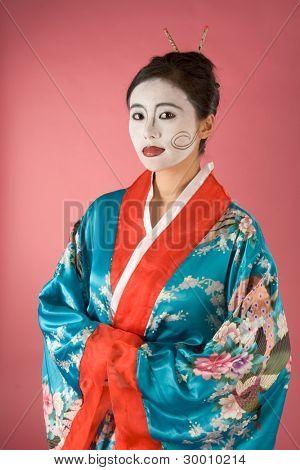 Asian female with geisha style face paint in yukata (kimono)