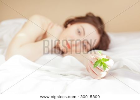 Woman Holding A Plant And Lying In Bed (focus On Sprout)