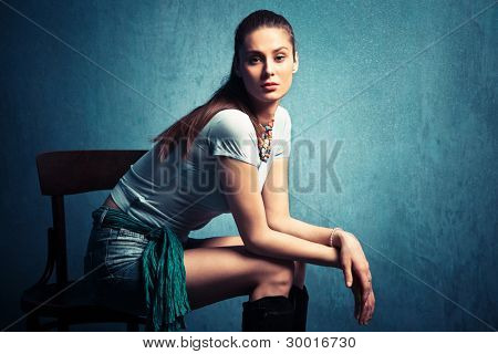 young nonchalant woman in shorts and t-shirt sit in empty room on old chair
