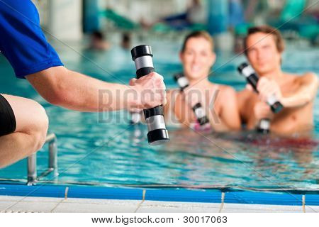 Fitness - a young couple (man and woman) doing sports and gymnastics or water aerobics under water in swimming pool or spa with dumbbells and instructor