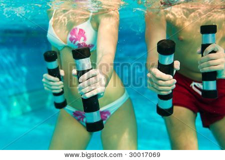 Fitness - a young couple (man and woman) doing sports and gymnastics or water aerobics under water in swimming pool or spa with dumbbells
