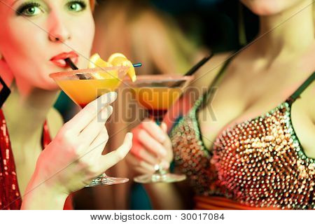 Women or models in club or disco with cocktails having fun, close-up on drinks