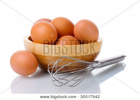 Metal whisk for whipping eggs and brown eggs in wooden bowl isolated on white