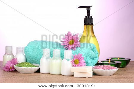 Hotel amenities kit on wooden table on purple background