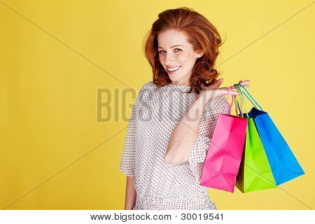 Happy smiling woman with three colourful shopping bags over her shoulder
