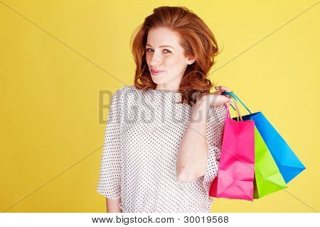 Beautiful redhead woman with a teasing expression carrying three colourful shopping bags over her shoulder.
