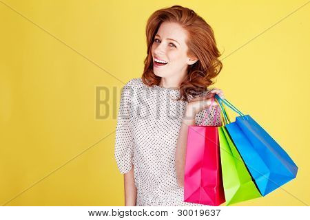 Laughing redhead woman standing with three colourful shopping bags over her shoulder