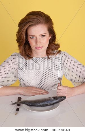 Upset woman holding her fork in her fist and looking angry about the whole raw fish she has been served on her plate