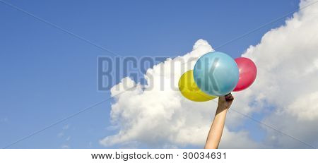 Girls Hand Holding Three Colorful Balloons