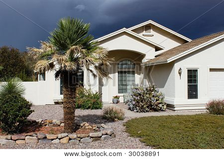 Ominous sky behind a sunlit Arizona home