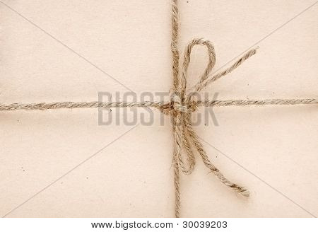 String tied in a bow on a brown paper