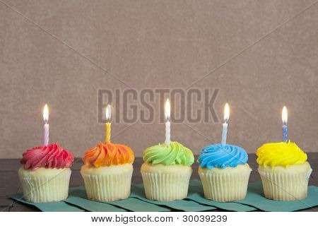 Five Brightly Colored Cupcakes with Lit Candles