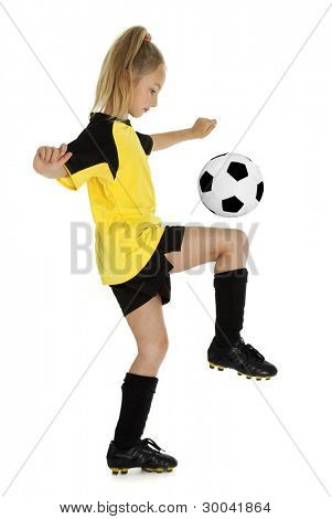 Full length side view of eight year old girl with soccer ball, isolated on white background.