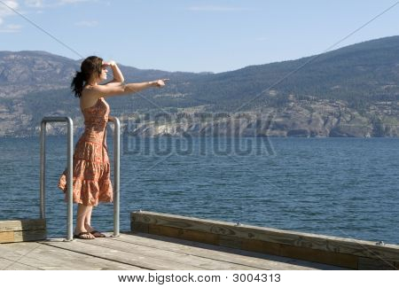 Pretty Woman Pointing By The Lake