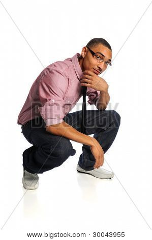 Portrait of young African American man crouching with hand on chin isolated over white background