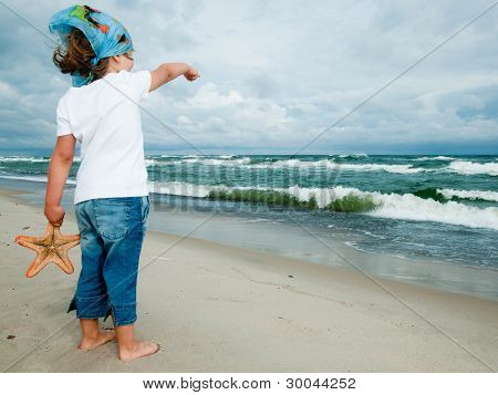 Summer vacation - lovely girl with starfish at the beach