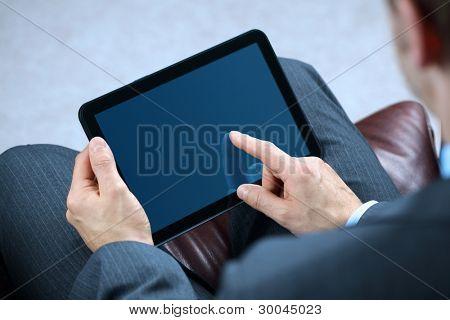 Kaufmann mit Finger berühren Schirm eine digitale Tafel, während auf einem Sofa sitzend