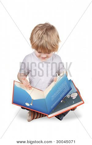 Young blonde 4 or 5 year old boy reading a picture book