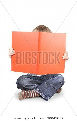 Boy holding up and hif=ding face behind big orange book isolated on a white background