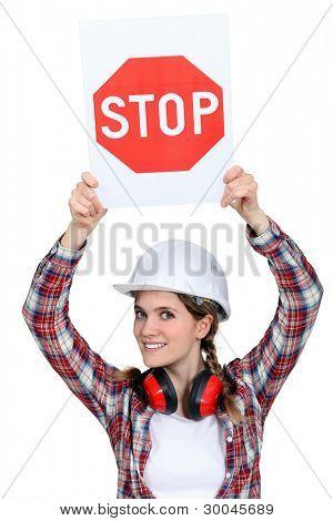 Female builder holding stop sign