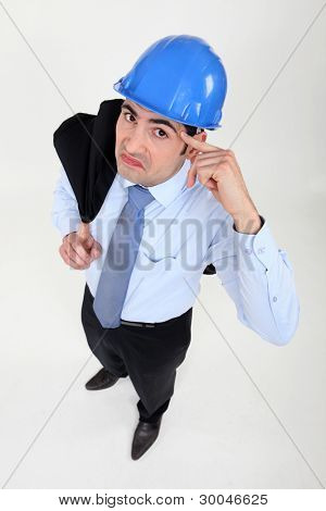 Engineer putting his finger to his head