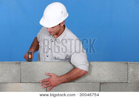 Man straightening brick wall