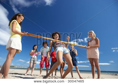Teenagers doing limbo dance on beach