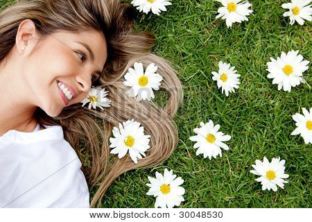 Beautiful woman lying in a garden of flowers