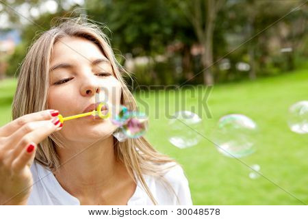 Young woman having fun blowing bubbles at the park