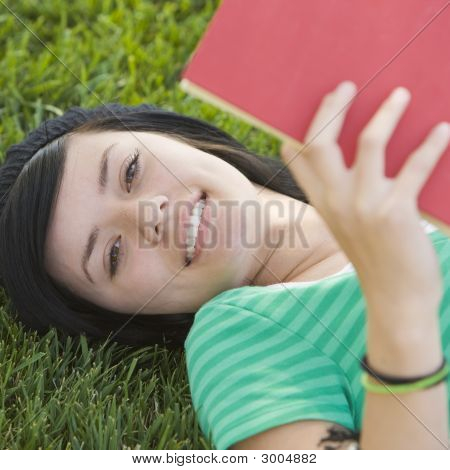 Teen Studies With Book In Grass