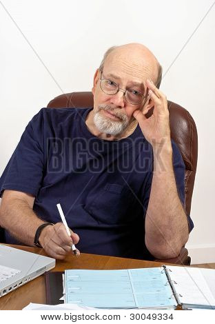 Senior Man With Checkbook Paying Bills And Worrying