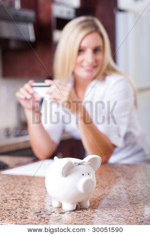young woman saving money, focus on piggybank