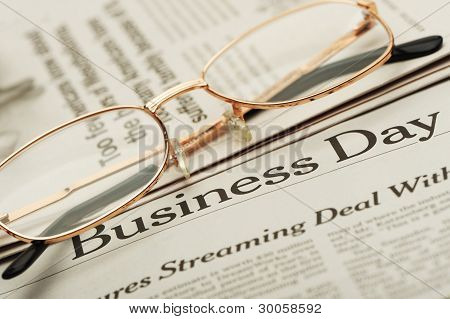 Eyeglasses Lie On The Newspaper With Title Business Day